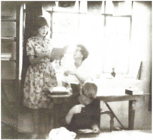 """The photograph above was taken in about 1965 inside the Presbyterian Church in Jemez Springs, where the original library was located before moving to a """"donated"""" room in the Jemez Mountains Electric Coop building. Patricia Evilsizer (assistant librarian) stands next to Grace Swetnam, seated. Jim Swetnam is at the table in the foreground. In addition to Patricia, Lupe Casaus also served volunteered as an assistant librarian."""