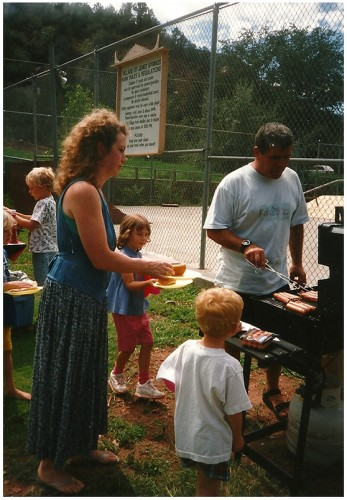 Nancy Blecha waits for the hot dogs cooked by Richard Barton.